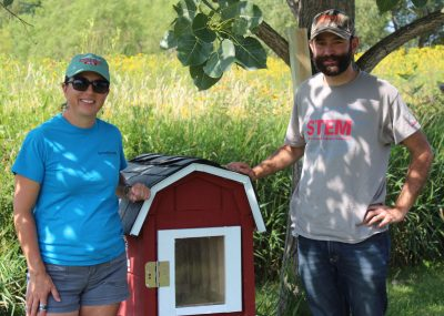 Normal Community High School teacher, Daniel Higby (right) and ISU Horticulture Center Coordinator, Jessica Chambers show off the new Little Free Library constructed by students and sponsored by McLean County Farm Bureau